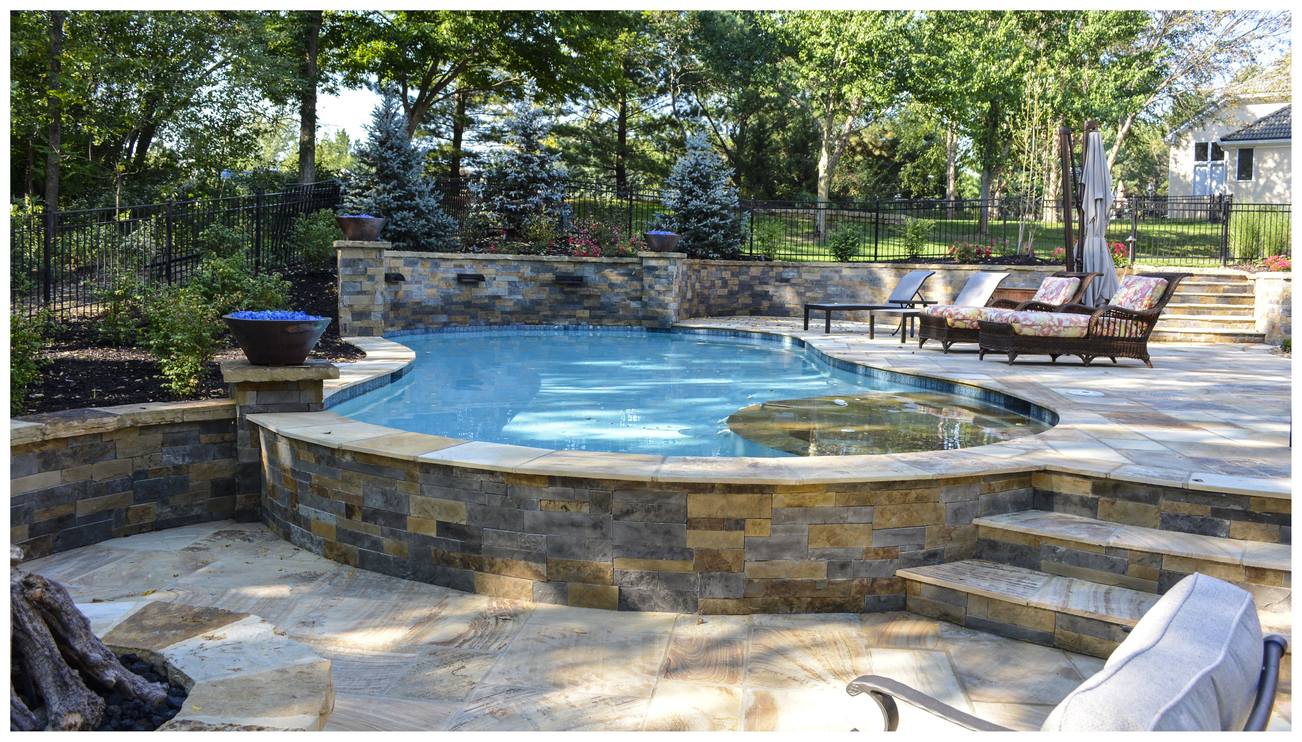 Freeform gunite pool with sun ledge and sheer descent waterfalls